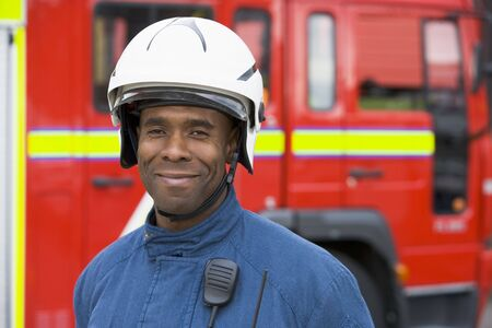 Fireman standing by fire engine wearing helmet photo