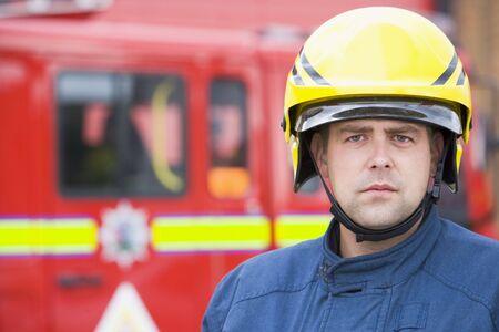 voiture de pompiers: Pompier debout par un incendie moteur port du casque  Banque d'images