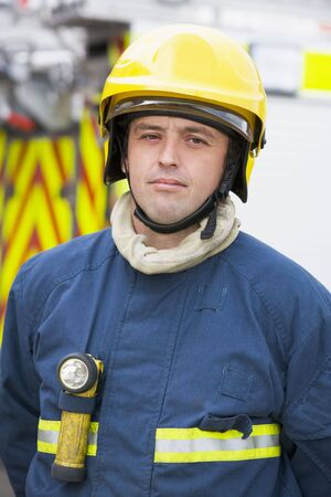 frontal views: Fireman standing by fire engine wearing helmet
