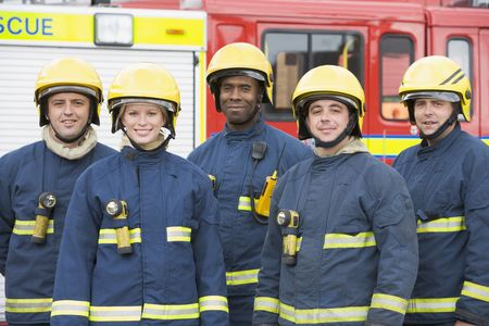 Five firefighters standing by fire engine wearing helmets photo