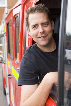 motor ardiendo: Los bomberos sesi�n en cami�n de bomberos con la cabeza a cabo ventana  Foto de archivo