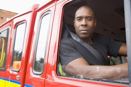 voiture de pompiers: Fireman assis dans le feu du moteur de recherche la fen�tre
