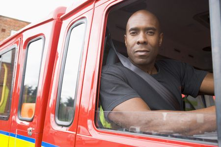 Fireman sitting in fire engine looking out window photo