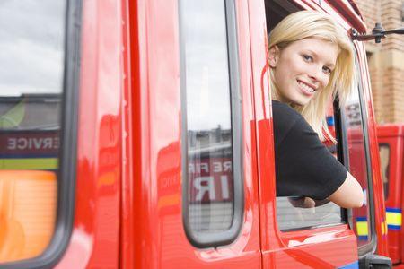motor ardiendo: Firewoman sesi�n en cami�n de bomberos con la cabeza a cabo ventana