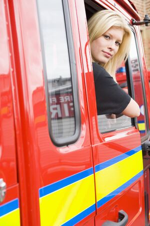 Firewoman sitting in fire engine with head out window photo