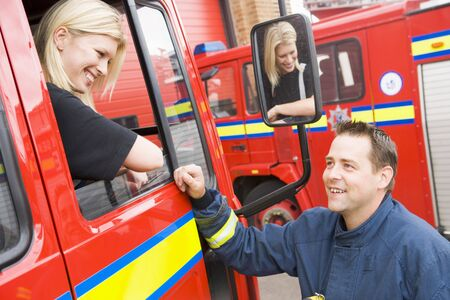 Firewoman sitting in fire engine talking to fireman standing outside photo