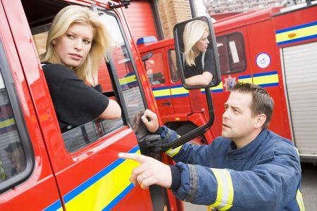 voiture de pompiers: Fireman pointant quelque chose � firewoman s�ance en cas d'incendie moteur