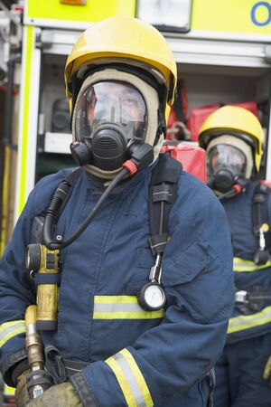 the field and in depth: Two firemen in masks standing near fire engine (depth of field)