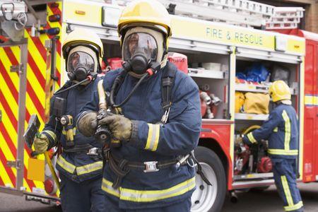 motor ardiendo: Dos bomberos con manguera y hacha a pie de cami�n de bomberos y otro bombero en el fondo (enfoque selectivo)  Foto de archivo