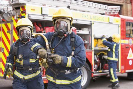 camion pompier: Deux pompiers avec tuyau et hache à pied de pompiers et un autre pompier en arrière-plan (sélective focus)  Banque d'images