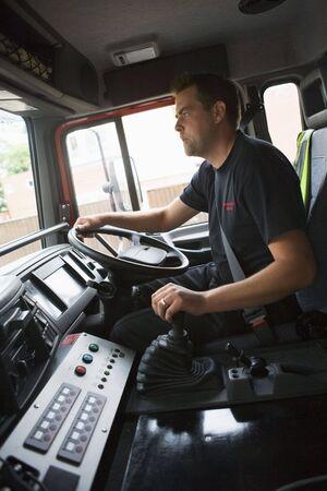 Fireman in fire engine holding steering wheel photo