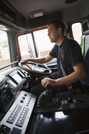 Fireman in fire engine holding steering wheel photo