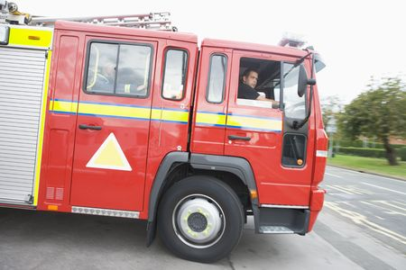 Firefighters driving fire engine out of driveway photo