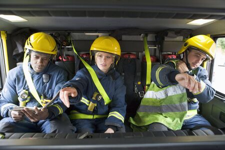 Three firefighters in fire engine wearing helmets with one pointing photo