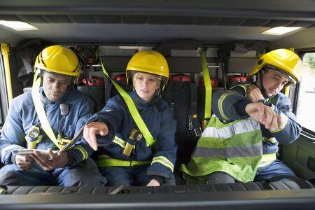 motor ardiendo: Tres bomberos cami�n de bomberos en el uso de cascos con uno apuntando