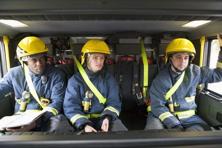 Three firefighters in fire engine wearing helmets with one reading photo