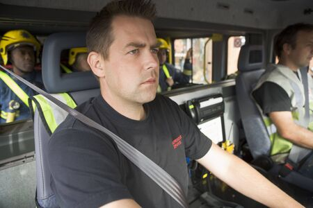Group of firefighters in fire engine with focus on passenger seat (selective focus) photo