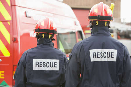 Two rescue workers standing near rescue vehicle photo