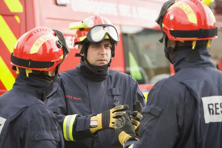 Three rescue workers talking by rescue vehicle photo