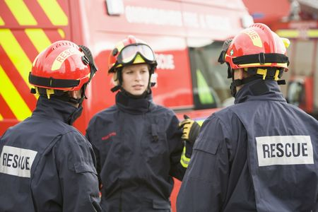 frontal views: Three rescue workers talking by rescue vehicle (selective focus)