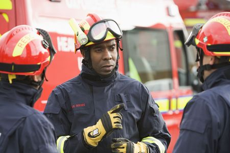 briefing: Three rescue workers talking by rescue vehicle (selective focus)