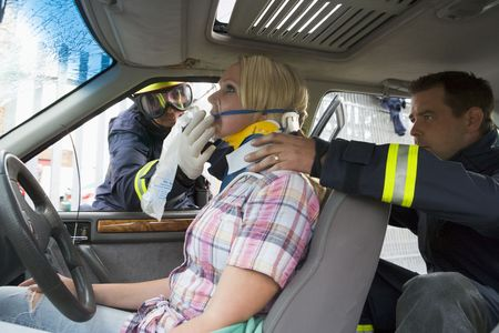 Two firemen helping a woman in neck brace breathe with oxygen mask photo
