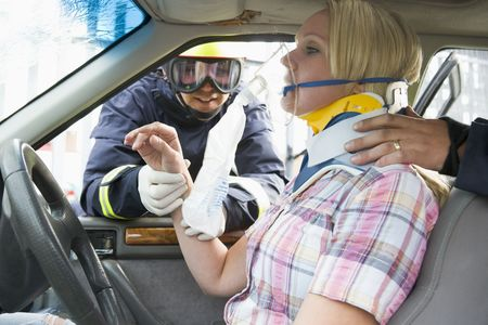 motorcars: Two firemen helping a woman in neck brace breathe with oxygen mask