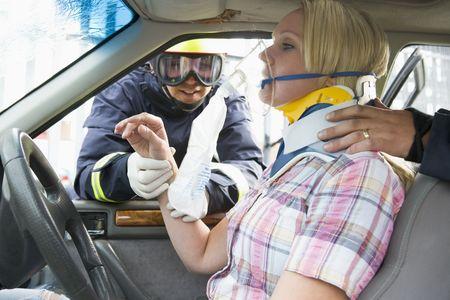 Dos bomberos ayudar a una mujer en el cuello ortopédico respirar con máscara de oxígeno