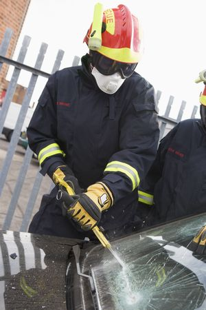 motorcars: Two firefighters cutting out a windshield after an accident Stock Photo