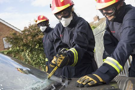 collisions: Two firefighters cutting out a windshield after an accident with another firefighter in background