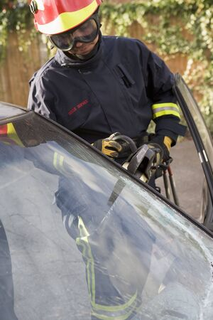 collisions: Firefighter cutting out a windshield after an accident Stock Photo