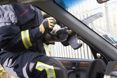 motorcars: Firefighter cutting out a windshield after an accident Stock Photo