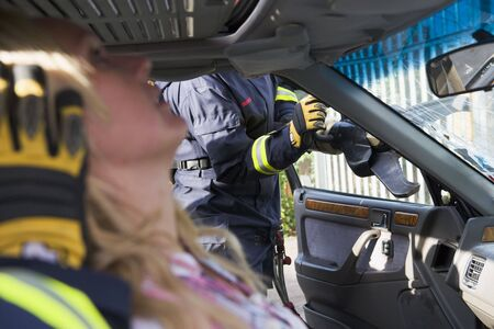 Firefighter cutting out a windshield after an accident with injured woman in foreground (selective focus) photo