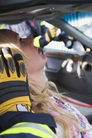 Injured woman in car with firefighter in background cutting out windshield (selective focus) Stock Photo - 3200704