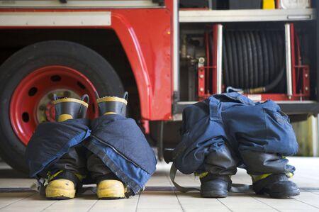 motor ardiendo: Dos uniformes de extinci�n de incendios en el piso por un incendio del motor Foto de archivo