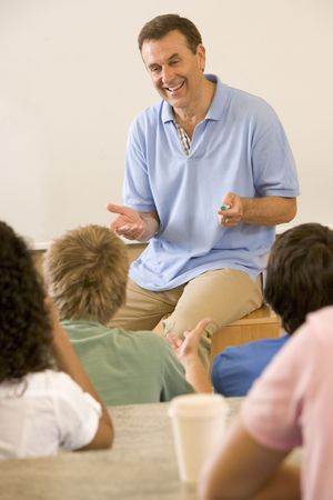 Teacher giving lecture to students in classroom (selective focus) photo
