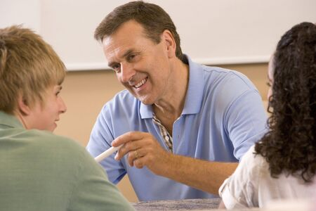 instructing: Teacher with two students in classroom