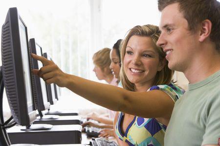 usando computadora: Cuatro personas sentadas en terminales de computadora (profundidad de campo  clave de alta)