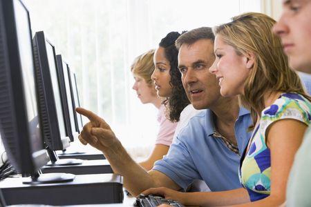 Cuatro estudiantes sentados en terminales de computadora con el maestro ayudar a uno de ellos (profundidad de campo / clave de alta)