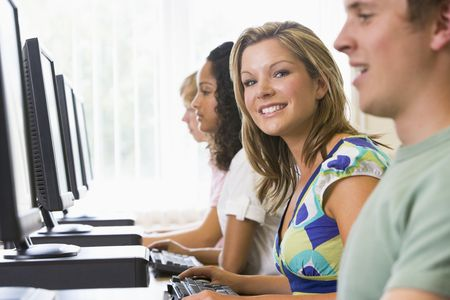 Four people sitting at computer terminals (selective focus/high key) Stock Photo - 3204902