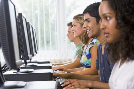 Four people sitting at computer terminals (selective focus/high key) Stock Photo - 3199480