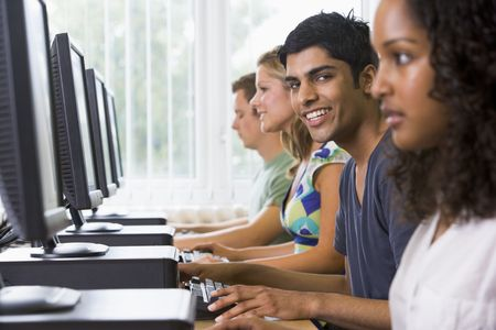 usando computadora: Cuatro personas sentadas en terminales de computadora (atenci�n selectiva  alto clave)  Foto de archivo
