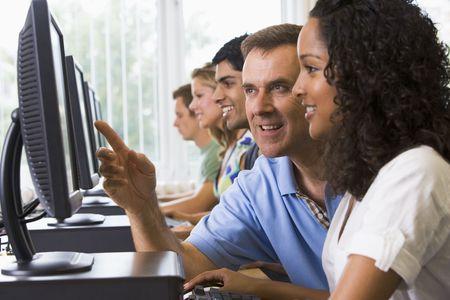 usando computadora: Cuatro estudiantes sentados en terminales de computadora con el maestro ayudar a uno de ellos (profundidad de campo  clave de alta)