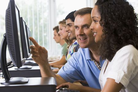 further: Four students sitting at computer terminals with teacher helping one of them (depth of fieldhigh key) Stock Photo