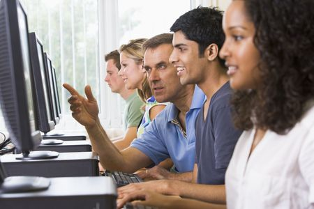 uses computer: Four students sitting at computer terminals with teacher helping one of them (depth of fieldhigh key) Stock Photo