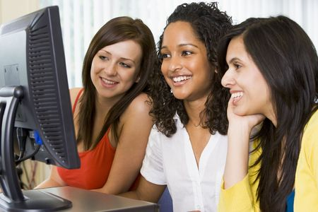 Three women sitting at a computer terminal (high key) photo