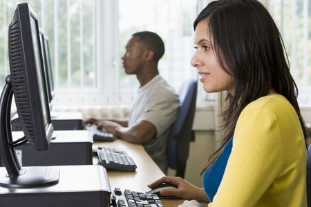 centres: Woman sitting at a computer terminal with man in background (selective focushigh key)