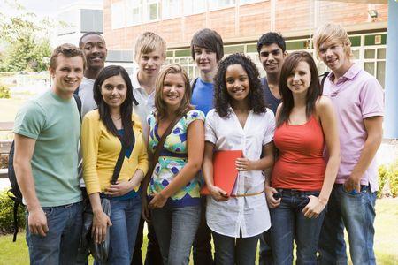 adolescentes chicas: Grupo de los estudiantes al aire libre buscando a c�mara sonriente