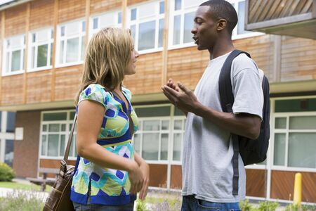 Two students standing outdoors talking photo