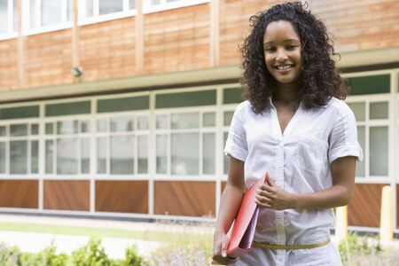 school campus: Student standing outdoors smiling and holding binder Stock Photo
